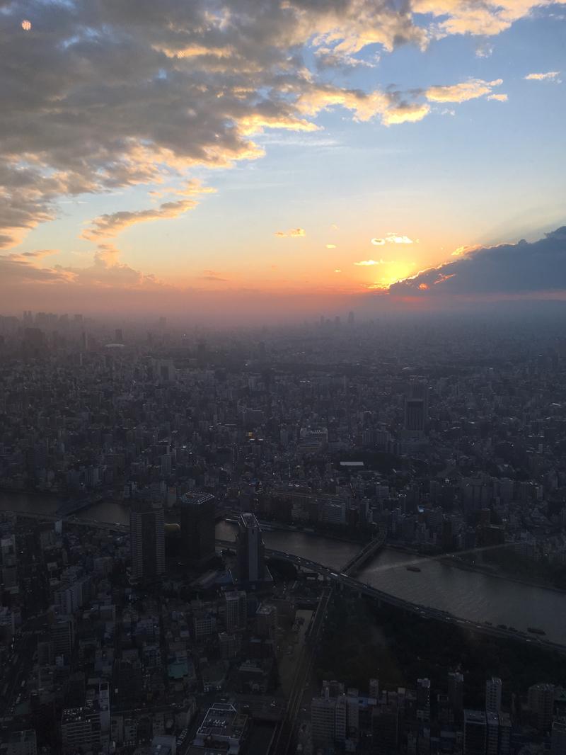東京スカイツリーから雲の合間に落ちていく夕日を眺める
