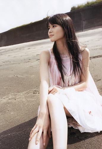 PINKのワンピで砂浜に座る矢島舞美