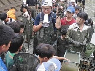 池の水抜きで捕獲したウシガエルの説明を受ける子供達