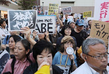JR秋葉原駅前でプラカードを手に「反安倍」を訴える人たち=19日午後、東京都千代田区