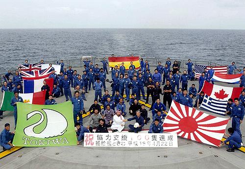 インド洋補給終了!洋上補給100隻を達成、給油した各国の旗を並べ記念写真に収まる海自の補給艦「ときわ」乗員(2003年4月22日)
