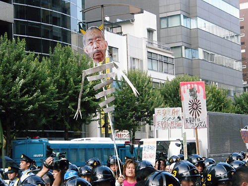 平成25年8月15日、反天連デモで先帝陛下(昭和天皇)の顔写真に、ツノを付け、身体を骸骨にした人形を笑いながら振り回すチョン顔丸出し野郎!(関連記事3))