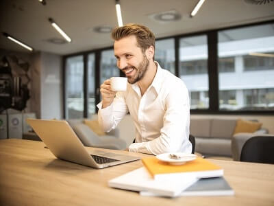 man-beard-smile-coffee-laptop-office.jpg