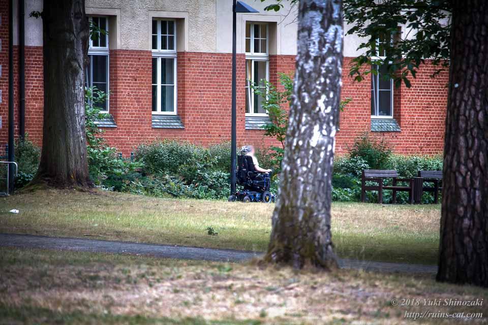 リハビリ施設の野外を散策する車椅子患者