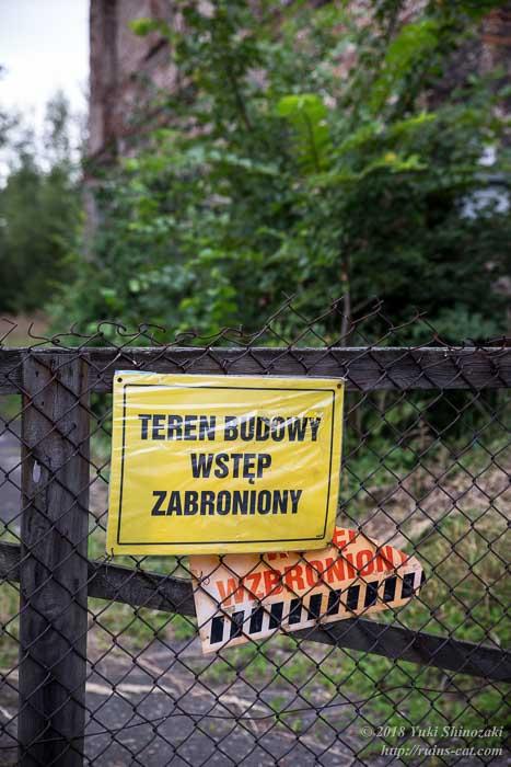 「建設現場への立ち入り禁止」とポーランド語で書かれた黄色い看板