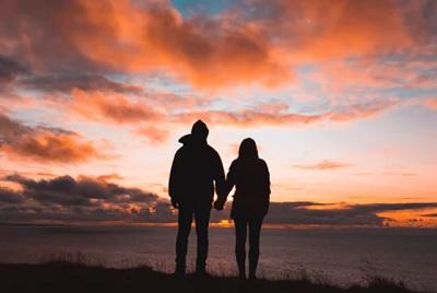 夕日をバックに手をつなぐカップル