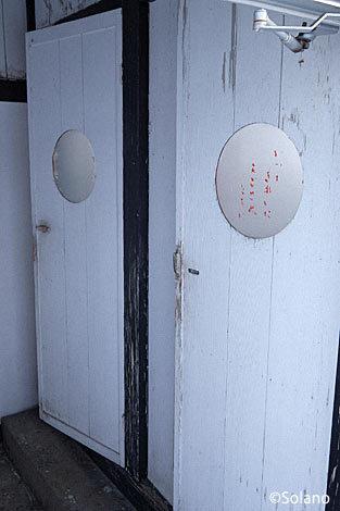 木の扉の丸窓がレトロで味のある雰囲気、上白滝駅のトイレ。